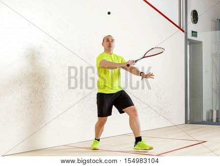 Young caucasian man playing squash. Slugger flying on top of the ball. It should be in half a turn to the camera looking up. Horizontal color image.