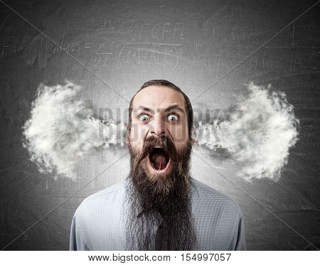 Portrait of shouting man with long beard and steam going out of his head. Concept of frustration
