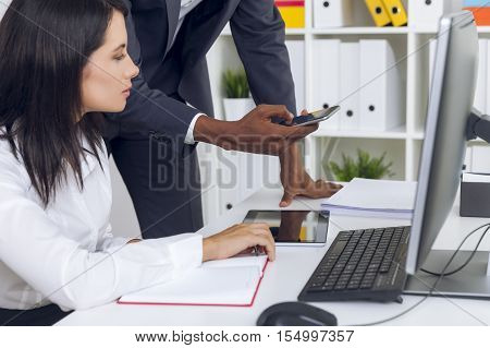 Woman Looking At Colleague's Phone.