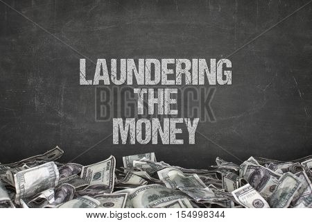 Laundering the money text on black background with dollar pile