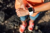 Trail runner athlete using her smart watch app to monitor fitness progress or heart rate during run  poster