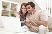 stock photo of voip  - Happy man and woman couple in their thirties sitting together at home on a sofa using a laptop computer to make a VOIP internet phone call and waving at the screen - JPG