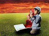 Two Muslims children sitting on meadow in Ramadan and reading Koran and praying