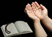 Hands up, islamic praying, Koran beside