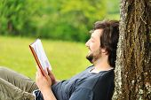 picture of reading book  - Young relaxed man reading book in nature - JPG