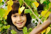 Happy childhood outdoor, happy faces between the leaves of the trees in forest or park, look for mor