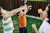 image of children playing  - Happy children playing with bubbles outdoor - JPG