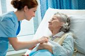 image of geriatric  - Nurse cares for a elderly woman lying in bed - JPG