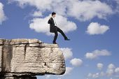 stock photo of adversity humor  - Businessman making a danger and step falling from a rock - JPG