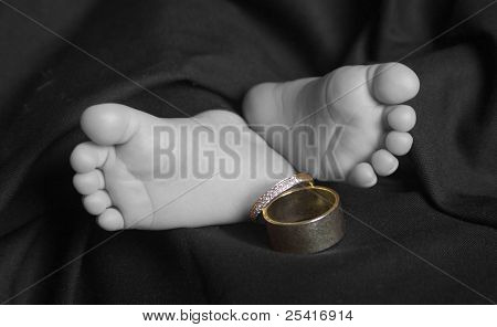Baby feet with parent's wedding rings selective color