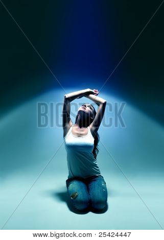 young woman looking upwards into blue spotlight