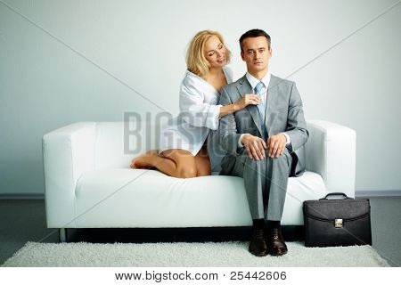 Photo of serious man sitting on sofa with seductive woman holding him by tie
