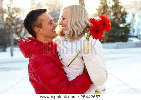 Photo of happy man embracing pretty woman with herberas outdoor in winter