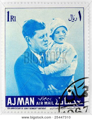 AJMAN - CIRCA 1967: A stamp printed in Ajman shows John F. Kennedy with his daughter Caroline Kennedy , circa 1967