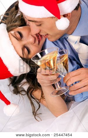 Young lovely couple in Santa hats holding the glasses of champagne and clinking glasses. Isolated over white background.