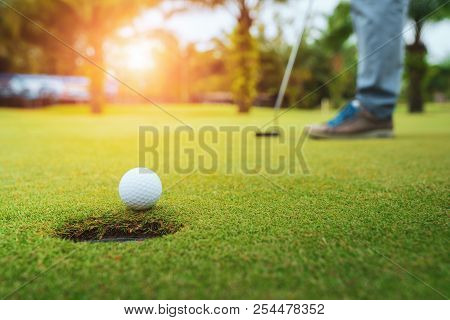 poster of Golfer Putting Golf Ball On The Green Golf, Lens Flare On Sun Set Evening Time, Pro Golf Long Puttin