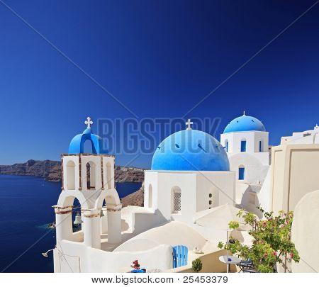 View of blue dome church in Oia village on Santorini island, Greece