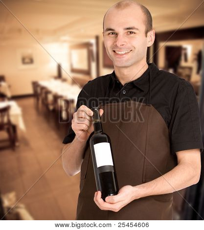 Smiling sommelier presenting a wine bottle with a blank label in a restaurant