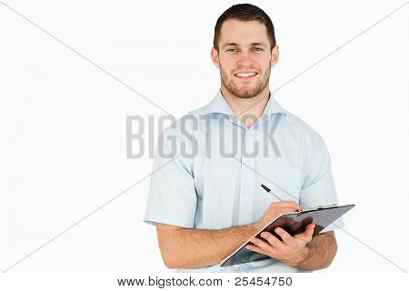 Smiling young post employee taking notes on clipboard against a white background