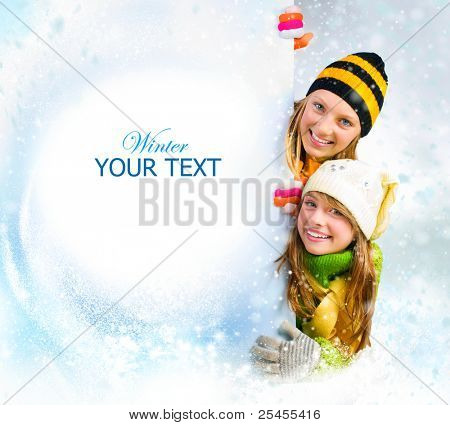 Winter teenage Girls peeking from behind blank sign billboard. Space for Your Text.Sale