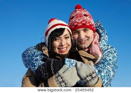 Portrait of happy couple in warm clothes embracing and looking at camera