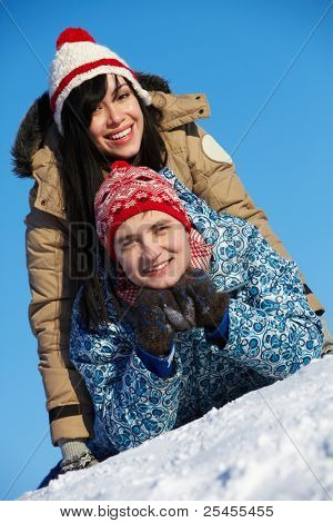 Portrait of happy couple in warm clothes having good time in winter