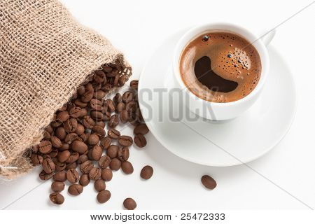 White coffee cup with jute bag and coffee beans