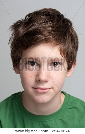 Portrait of a cute teenage boy with face covered with pimples.