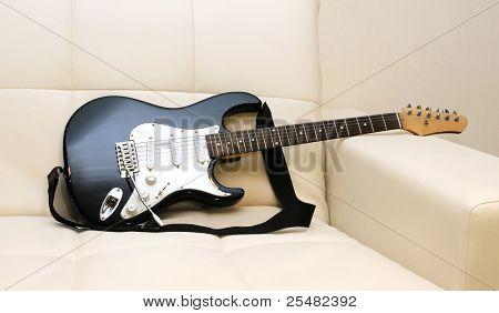 guitar on a leather sofa