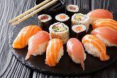 Постер, плакат: Set Of Sushi And Rolls With Salmon And Tuna Avocado California Maki Soy Sauce Chopsticks Close