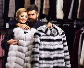 Man With Strict Face And Woman With Coats In Fur Shop. Woman With Smiling Face In Black Fur Coat Wit poster