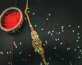 Rakhi With Rice Grains, Kumkum  With Wooden Background And With Elegant Rakhi. A Traditional Indian  poster