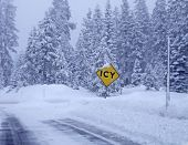 stock photo of icy road  - Landscape with road in winter forest and road sign  - JPG