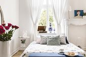 Drapes At Window Above Bed With Cushions In White Bedroom Interior With Poster And Roses. Real Photo poster