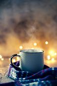 Cozy Atmosphere With Winter Coffee Or Tea Mug With Steam Covered With Wool Scarf Over Bokeh Lights poster