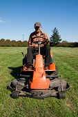 picture of grass-cutter  - Mature man driving grass cutter in a sunny day - JPG