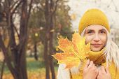 Young Autumn Woman Holding Yellow Maple Leaf And Smiling Outdoors. Cute Girl In Yellow Hat And Scarf poster