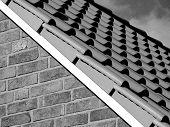 pic of roof tile  - A close-up of a tiled roof on a brick house.