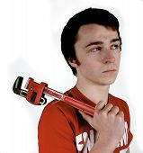stock photo of roustabouts  - Young worker holding a Stillson wrench thinking about the job to be done - JPG