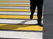 Male Legs On The Pedestrian Crossing. Man In A Black Business Suit Crossing The Street At A Crosswal poster