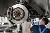 Car Mechanic Inspecting Car Wheel And Repair Suspension Detail. Lifted Automobile At Repair Service  poster