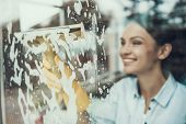 Young Smiling Woman Washing Window With Sponge. Happy Beautiful Girl Wearing Protective Gloves Clean poster