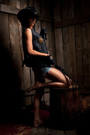 picture of atonement  - Beautiful sexy woman with  Black Leather Flogging Whip in cowboy hat and Shorts against wooden background - JPG
