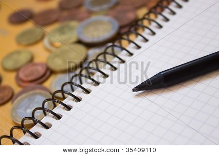 Pencil On Notebook And Money