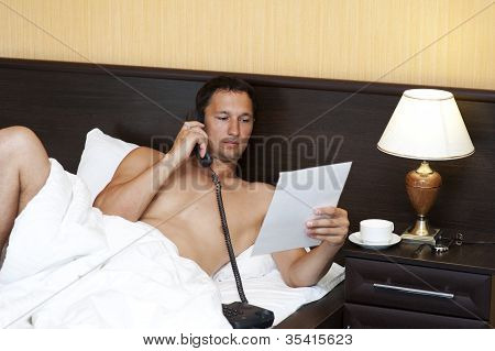 Relaxed Man In Bed Calling By Phone