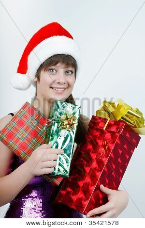 Attractive Girl In A Christmas Hat With Gift Boxes