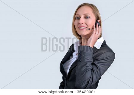 Successful Businesswoman With Headphone Talking On Phone In Her Office