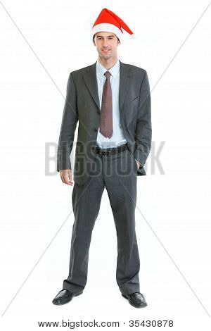 Full Length Portrait Of Smiling Businessman In Santa's Hat