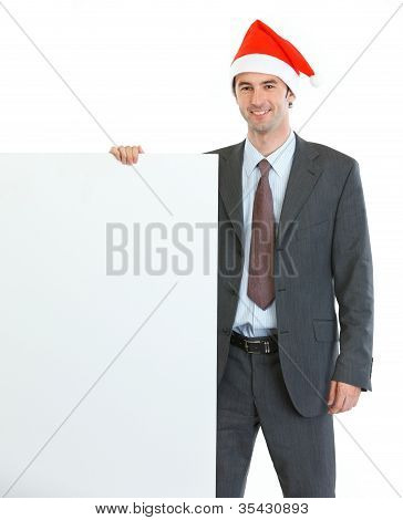 Smiling Businessman In Santa's Hat Showing Blank Billboard