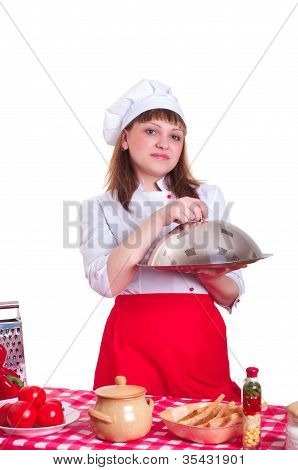 female chef holding a metal plate